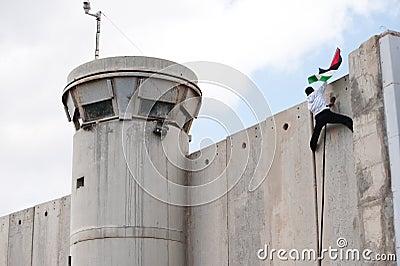 Palestinian climbs Israeli separation wall Editorial Photography