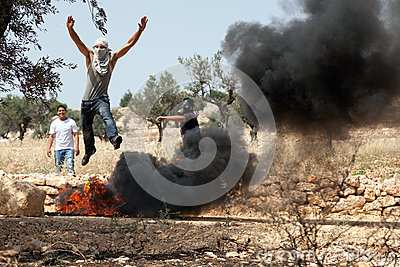 Palestinian Man Jumping over Fire at Protest Editorial Photo