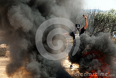 Palestinian Protester with Slingshot Amidst Smoke Editorial Photography