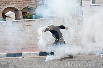 Palestinian throws back tear gas Editorial Photography