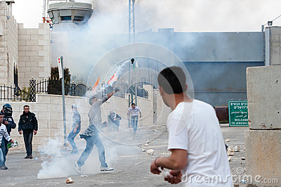 Palestinians throw back tear gas Editorial Stock Image