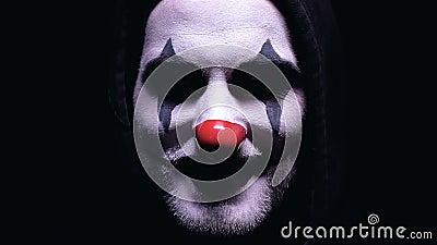 Palhaço assustador que sorri na câmera isolada no fundo preto, horror, close-up video estoque