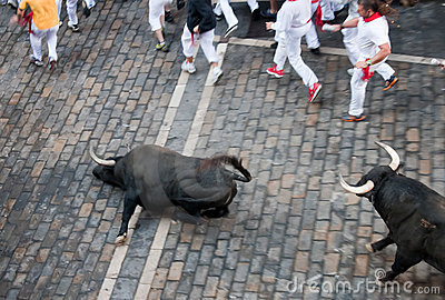 PAMPLONA, SPAIN -JULY 8: Bulls run down the street Editorial Stock Image