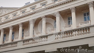 Classical Building With Snow Falling. Pan across the front of a large old building in snowfall stock video