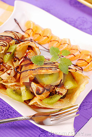 Pancakes with fruits poured with chocolate