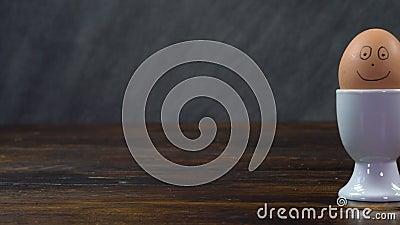 Panning som skjutits över ett träbord till ett kokt ägg i en vit äggkopp som har ett leende ansikte. stock video