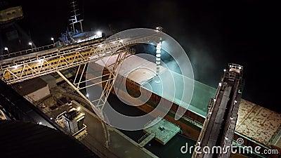 Panorama da noite de colheitas de grão da carga no navio maioria do cargueiro através do tronco para abrir posses da carga no ter filme