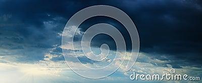 Panorama - sunbeams in stormy dark cloudy sky