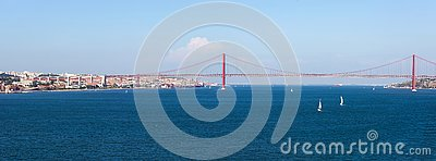 Panorama view over the 25 de Abril Bridge. The bridge is connecting the city of Lisbon to the municipality of Almada Stock Photo