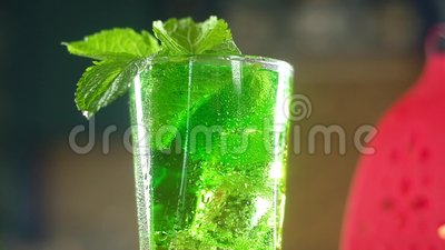 Panoramabild aus kohlensäurehaltigem grünem erfrischenden Cocktail mit Minzblättern, Eiswürfeln stock footage