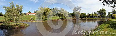 Panoramic view of a house with a pond