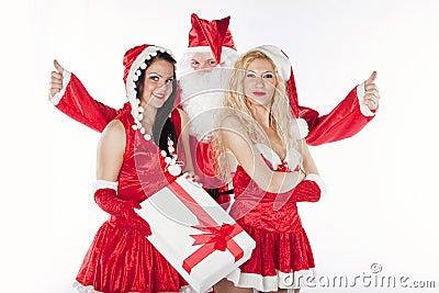Papá Noel con dos ayudantes atractivos en su oficina