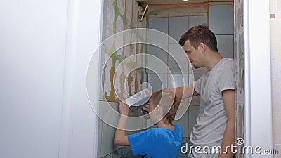 Pap en zoon maken samen renovatie thuis, verwijderen tegels van muren in de wc stock footage