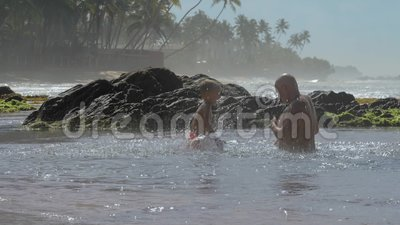Papa et mon garçon s'amusent à éclater de l'eau dans un océan tranquille clips vidéos