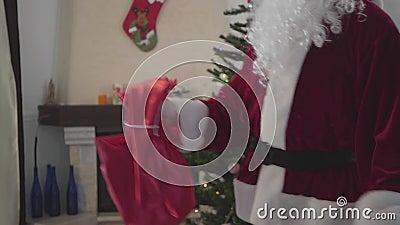 Papai Noel Caucasiano não reconhecível dançando em frente à árvore de Natal com sua bolsa de presentes Conceito de feriados feliz vídeos de arquivo