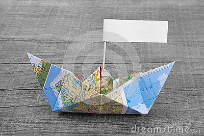 Paper boat folded out of a map with a time-out sign on an grey w