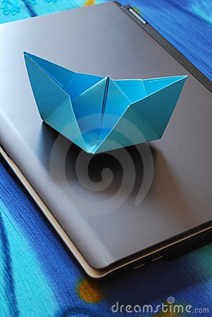 Paper boat sailing on laptop