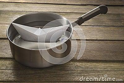 Paper boat sailing in a saucepan