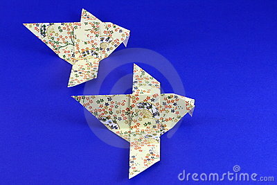 Paper origami birds on blue