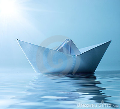 Paper ship in water and sunny blue sky