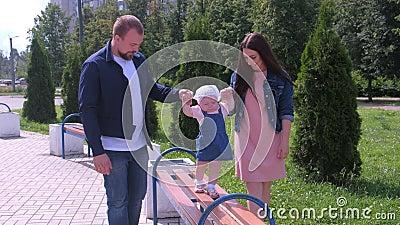 Pappa och mamma håller hand om en liten flicka som går i bänk i parken på sommaren arkivfilmer