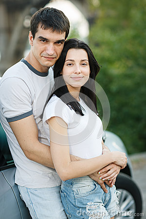 Par som plattforer utanför deras bil i omfamning