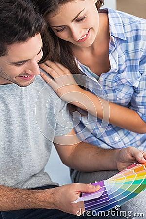 Par som ser färgprövkopior för att dekorera deras hus