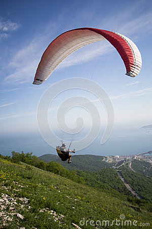 Free Paraglider Jumps From The Mountain To The Sea, Blue Sky, Warm Breeze, A Parachute, Stock Images - 43530074