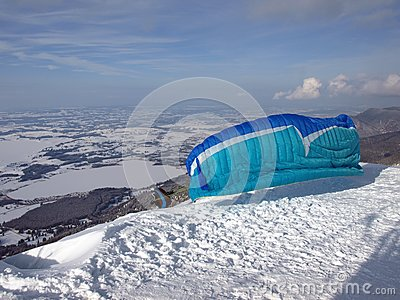 Paraglider running down a slope on a mountain