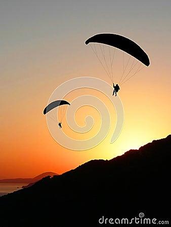 Paragliders in sunset coastal landscape