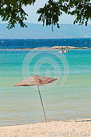 Paraguas de madera de la estera en la playa