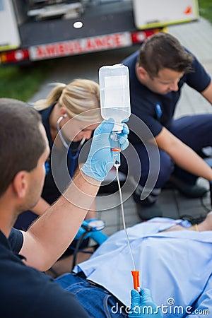 Paramedic team preparing drip for injured patient