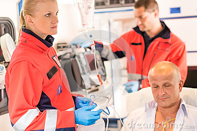 Paramedics in ambulance with patient heart attack