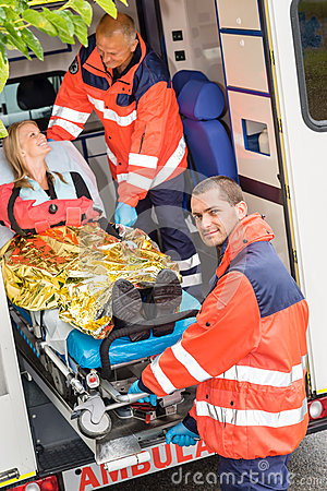 Paramedics helping woman on stretcher in ambulance