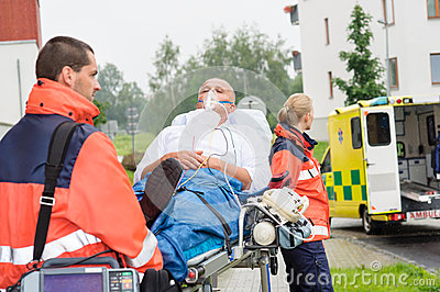 Paramedics with patient on stretcher ambulance aid