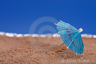 Parasol on beach sand with sea and blue sky