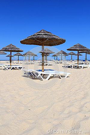 Parasol and sun loungers on Algarve beach