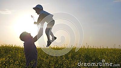 Parent engañar con el hijo en el prado, papá feliz con el muchacho que juega en juego del campo, del papá y del hijo del fondo en almacen de video