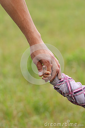 Parent holds the hand of a  child
