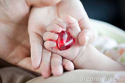 Parent s and baby s hands with heart