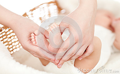 Parent s hands keeping newborn baby s feet