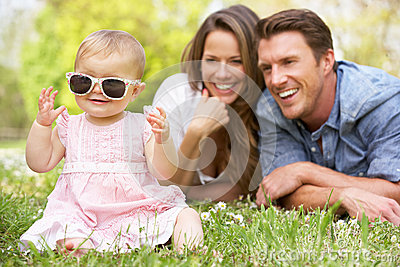 Parents With Baby Girl Sitting In Field
