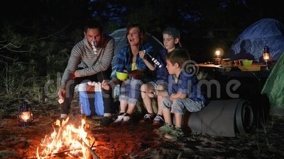 Parents with childs broil marshmallow on campfire to woodland, happy family fry marshmallow at fire. In travel camp in forest, mom and daddy with kids resting stock video footage