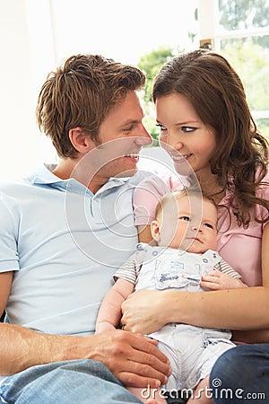 Parents Cuddling Newborn Baby Boy At Home