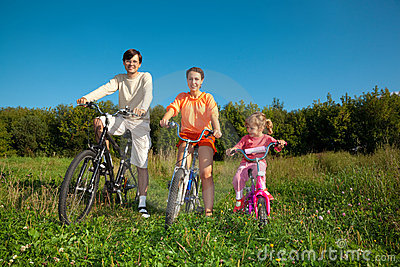 Parents with daughter on bicycles in park, day.