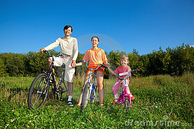 Parents with daughter on bicycles in park, day