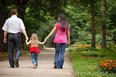 Parents with daughter walk on summer garden