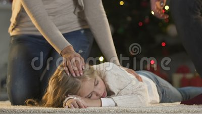 Parents de soin frottant peu de fille dormant près des cadeaux d'attente de pente d'arbre de Noël banque de vidéos