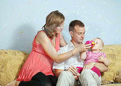 Parents feeding her   baby with bottle