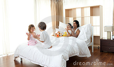Parents having breakfast and children playing